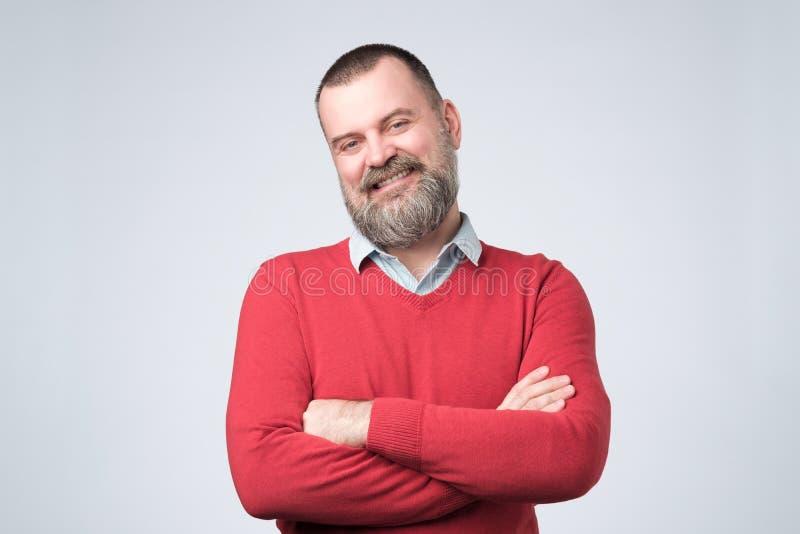 Hombre maduro con la barba que lleva a cabo las manos cruzadas y que mira la c?mara mientras que sonr?e fotografía de archivo libre de regalías