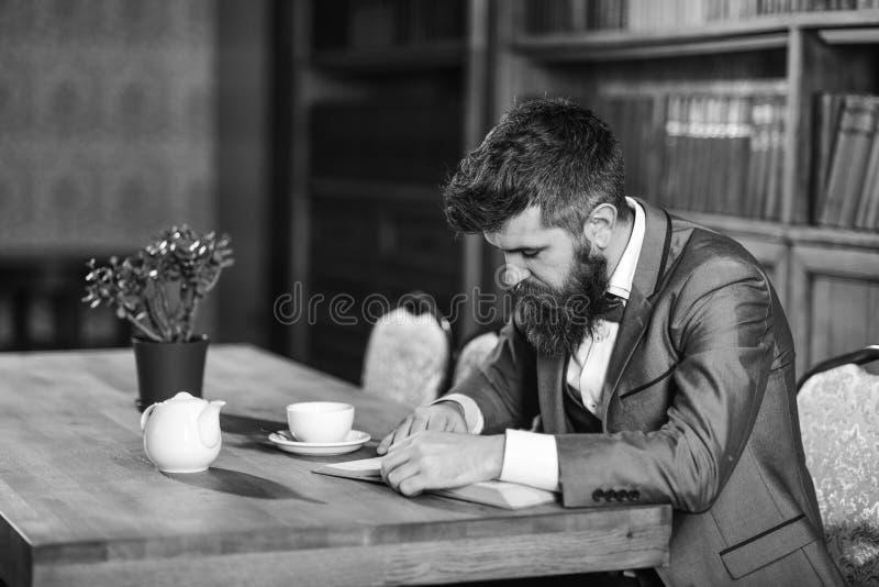 Hombre maduro con la cara pensativa y la barba larga Literatura, estudio, trabajo, investigación, concepto de la educación imágenes de archivo libres de regalías