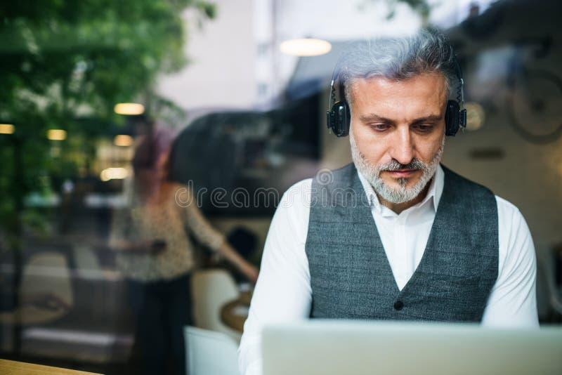 Hombre maduro con los auriculares en la tabla en un café, usando el ordenador portátil imagen de archivo libre de regalías