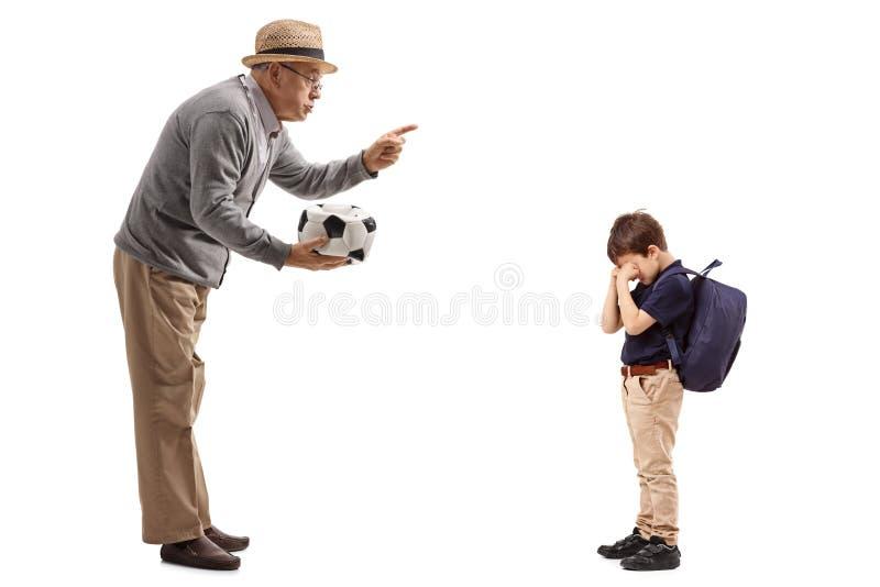 Hombre maduro con un fútbol desinflado que regaña a un niño pequeño imagen de archivo libre de regalías