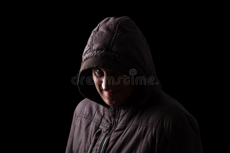 Hombre maduro con una sonrisa asustadiza y espeluznante que oculta en las sombras imagenes de archivo