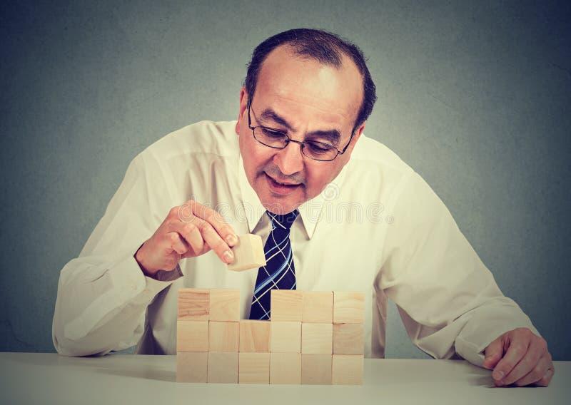 Hombre maduro concentrado que construye un negocio imágenes de archivo libres de regalías