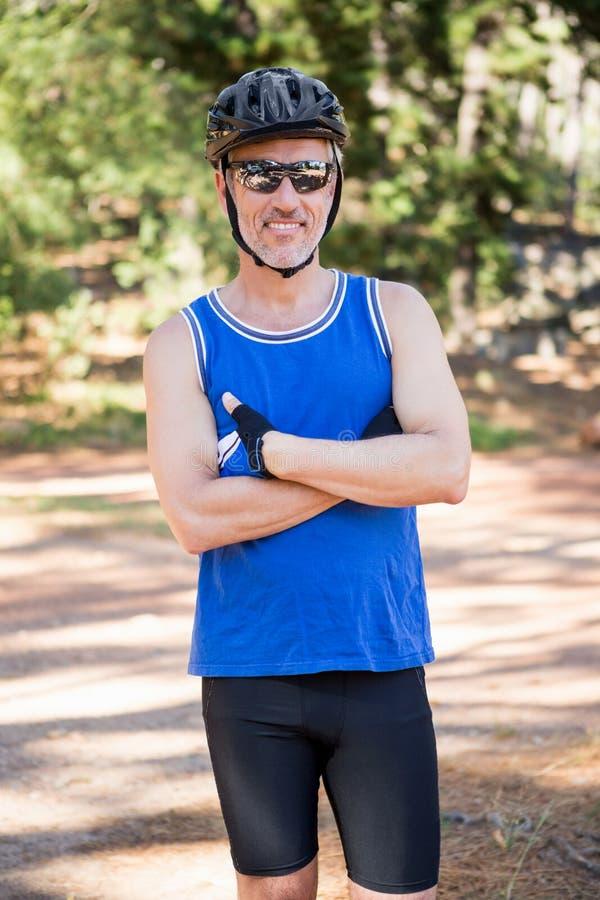 Hombre maduro del jinete de la bici que presenta con los brazos cruzados foto de archivo