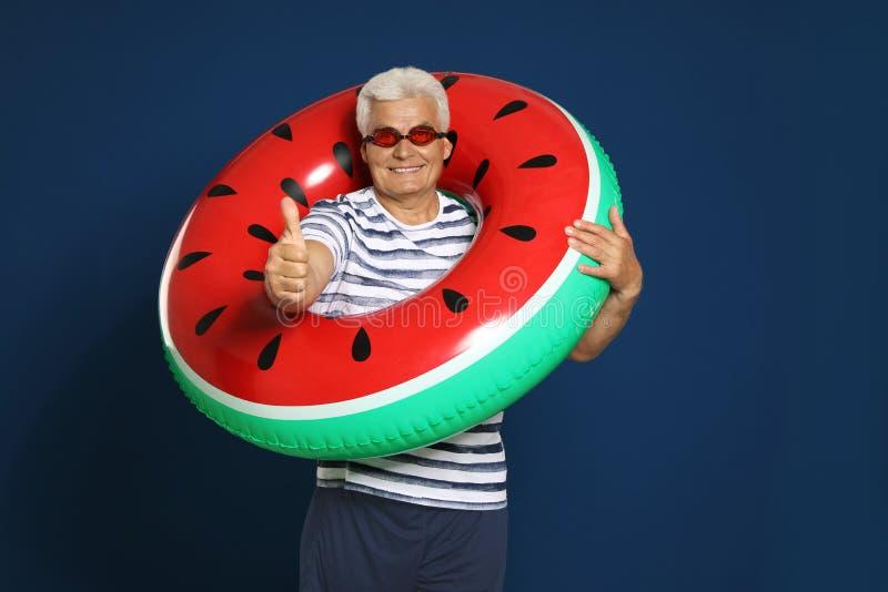 Hombre maduro divertido con el anillo inflable brillante en fondo azul fotos de archivo
