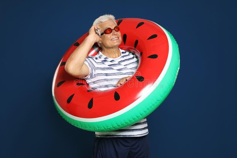Hombre maduro divertido con el anillo inflable brillante que habla en el teléfono en azul marino fotografía de archivo libre de regalías
