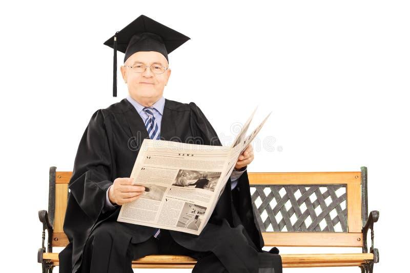 Hombre maduro en el periódico de la lectura del vestido de la graduación asentado en banco imágenes de archivo libres de regalías