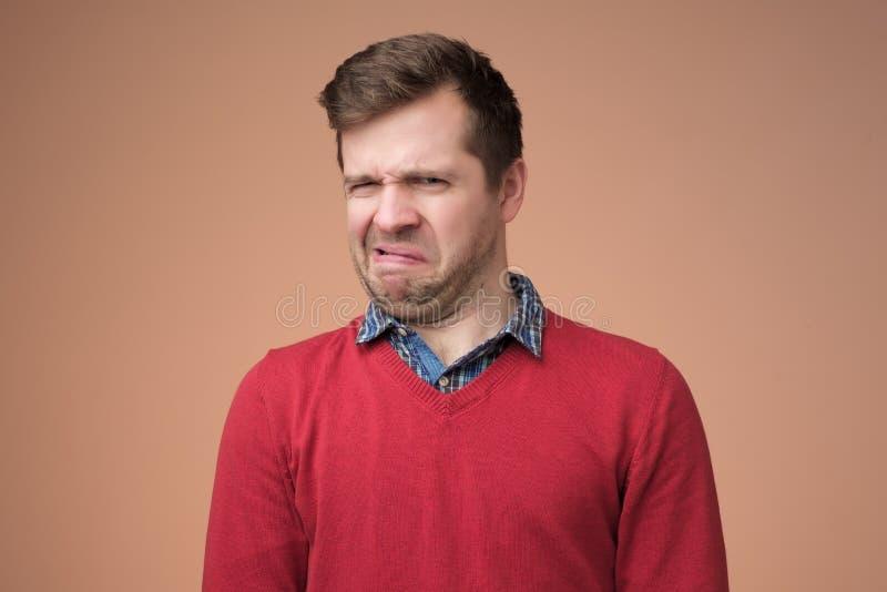 Hombre maduro en el suéter rojo que mira con la expresión de la incredulidad foto de archivo libre de regalías