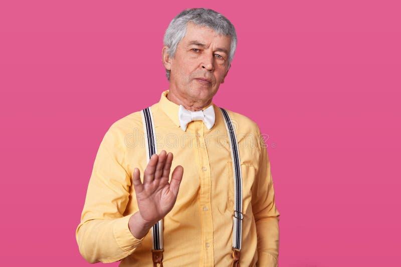 Hombre maduro en la camisa amarilla, las ligas y el bowtie blanco mostrando la muestra de la parada con la mano Niegue para hacer imagen de archivo libre de regalías