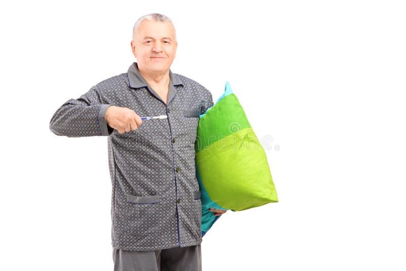 Hombre maduro en los pijamas que sostienen un cepillo de dientes y una almohada fotos de archivo
