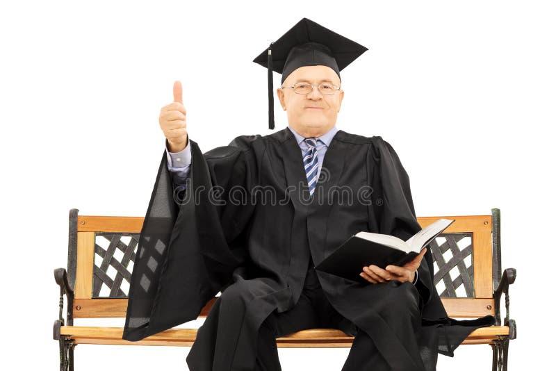 Hombre maduro en vestido de la graduación en el banco que da un pulgar para arriba imagen de archivo