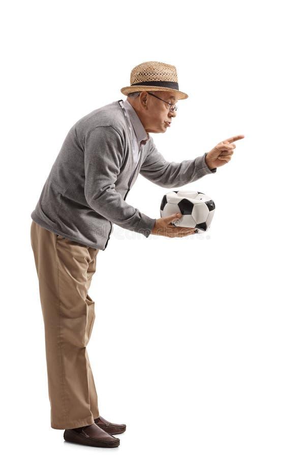 Hombre maduro enojado que lleva a cabo un fútbol desinflado y que regaña el someon foto de archivo
