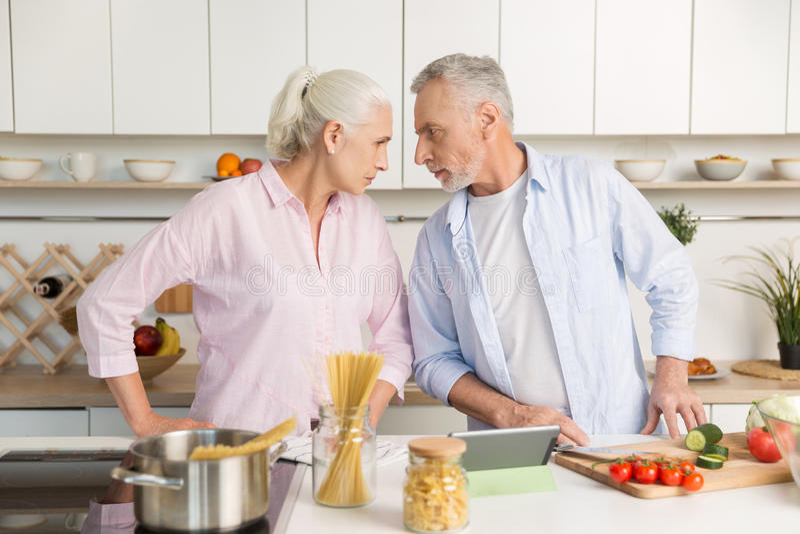 Hombre maduro enojado que se coloca cerca de mujer seria madura en la cocina fotografía de archivo