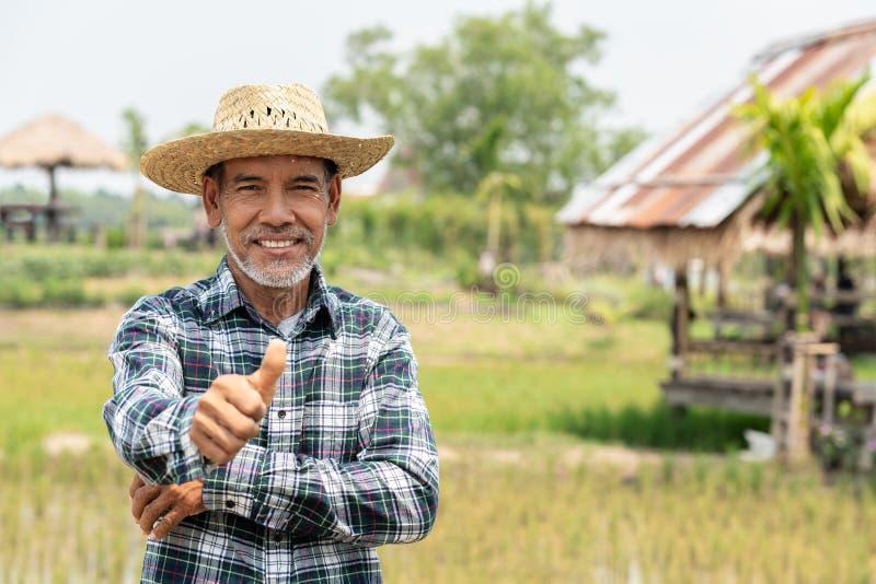 Hombre maduro feliz del retrato el más viejo está sonriendo Viejo granjero mayor con el pulgar de la barba blanca encima de senti imagen de archivo