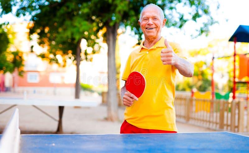 Hombre maduro feliz que juega a tenis de mesa y que muestra el pulgar para arriba imágenes de archivo libres de regalías