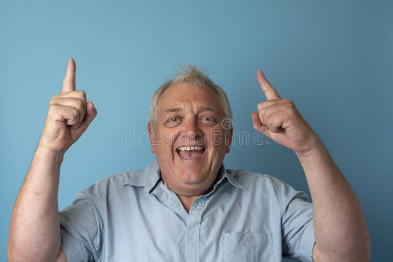 Hombre maduro feliz que sonríe y que señala fotos de archivo libres de regalías