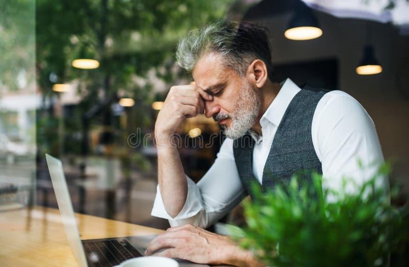 Hombre maduro frustrado que se sienta en la tabla en un café, usando el ordenador portátil fotos de archivo libres de regalías