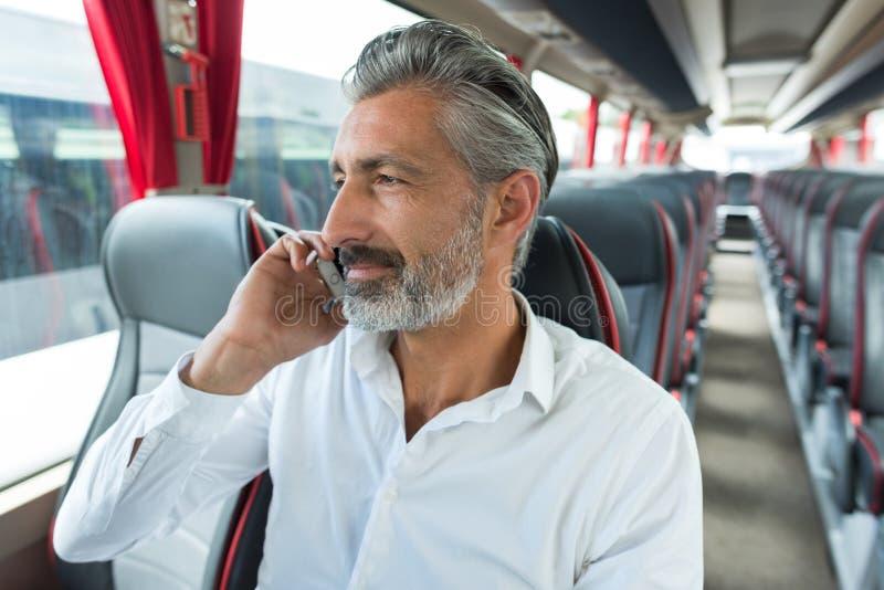 Hombre maduro hablando en celular en bus vacío imagen de archivo