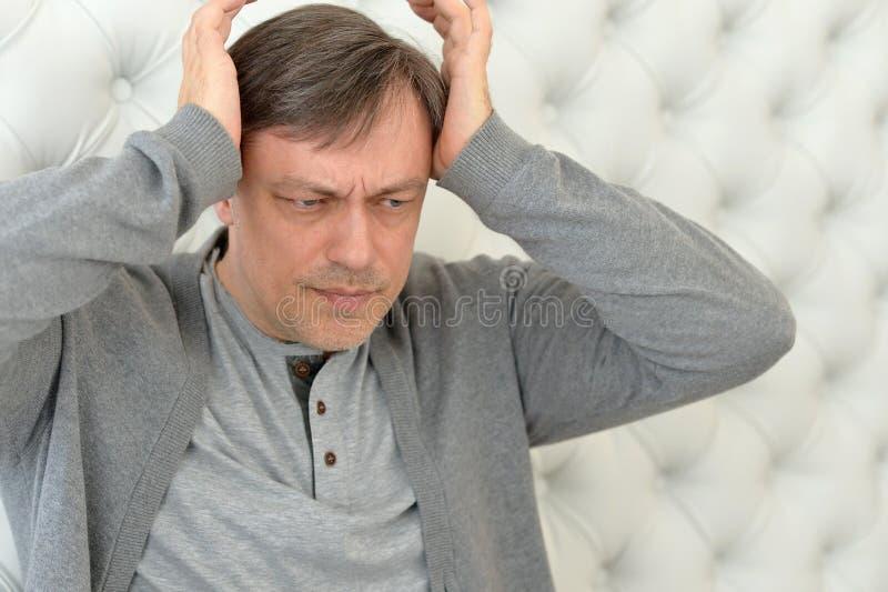 Hombre maduro hermoso con dolor de cabeza foto de archivo