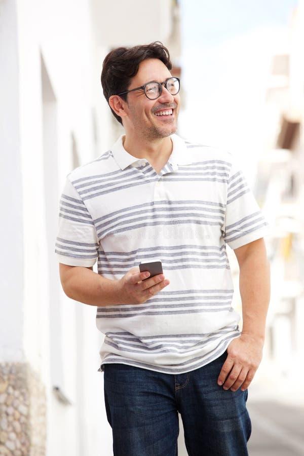 Hombre maduro hermoso que camina con el teléfono celular en la ciudad fotografía de archivo libre de regalías