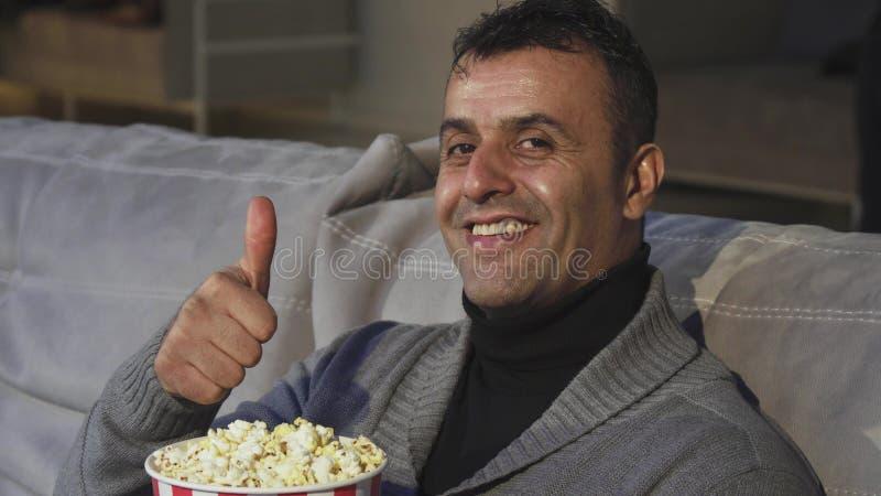 Hombre maduro hermoso que muestra los pulgares para arriba mientras que se sienta en el cine imágenes de archivo libres de regalías