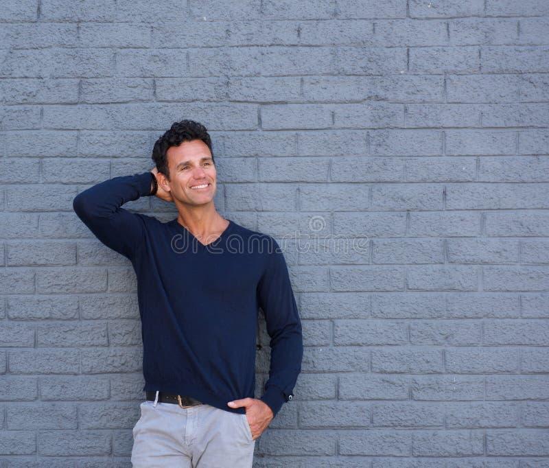 Hombre maduro hermoso que sonríe con la mano en pelo fotos de archivo