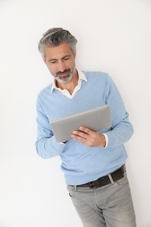Hombre maduro hermoso que usa la tableta aislada imagenes de archivo