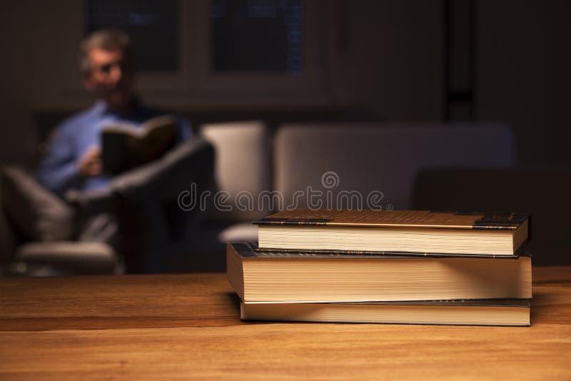 Hombre maduro leyendo un libro en una sala de estar de noche imagen de archivo libre de regalías