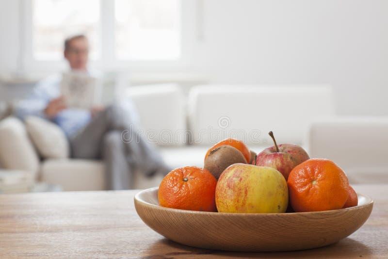 Hombre maduro leyendo un periódico en una sala de estar con cuenco de fruta en primer plano fotos de archivo