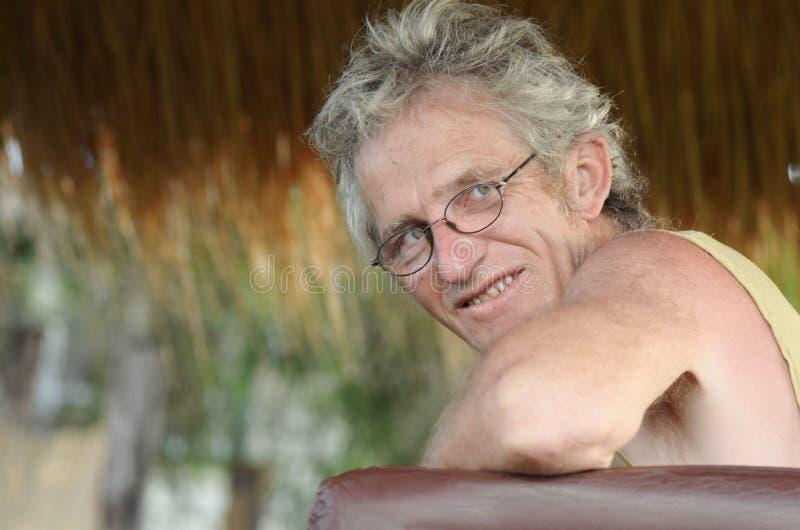 Hombre maduro mayor y sonrisa relajada de las gafas foto de archivo