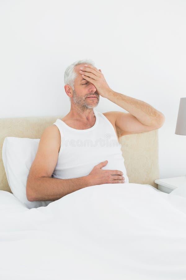 Hombre maduro pensativo que se sienta en cama fotos de archivo