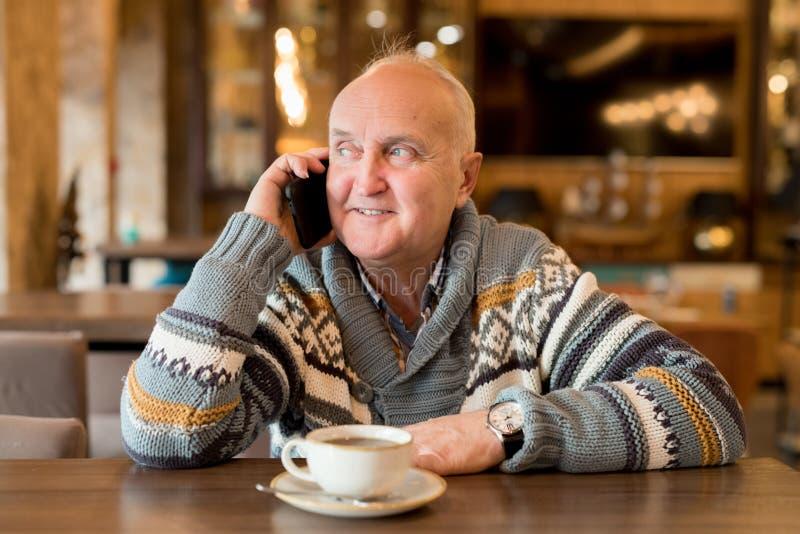 Hombre maduro positivo que habla por el teléfono móvil fotos de archivo libres de regalías