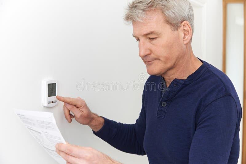 Hombre maduro preocupante con Bill Turning Down Heating Thermostat foto de archivo