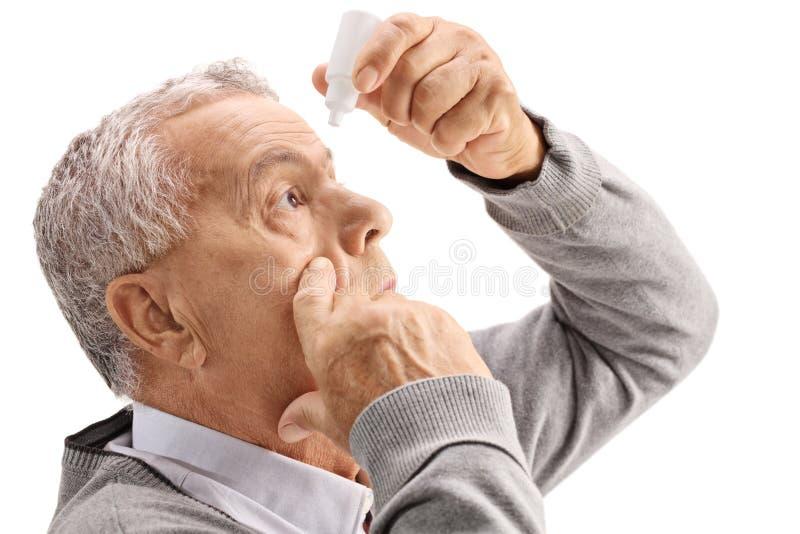 Hombre maduro que aplica descensos de ojo foto de archivo libre de regalías