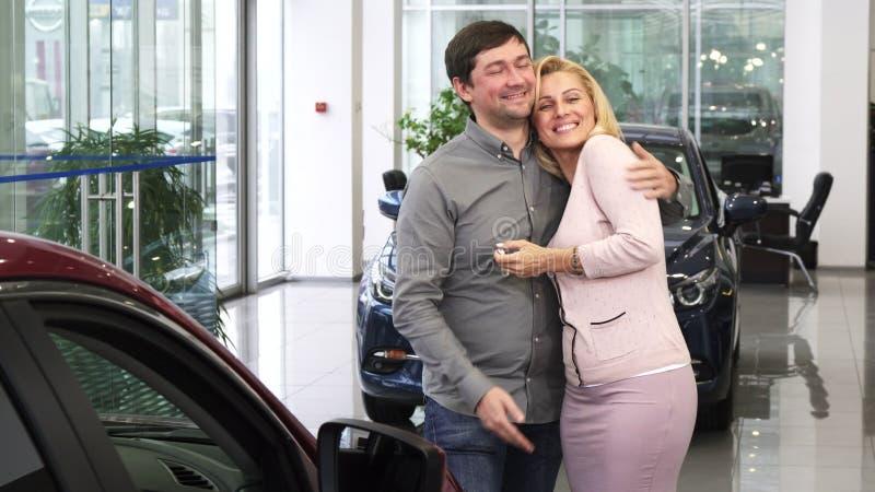 Hombre maduro que compra un nuevo coche para su esposa magnífica en el salón de la representación imágenes de archivo libres de regalías