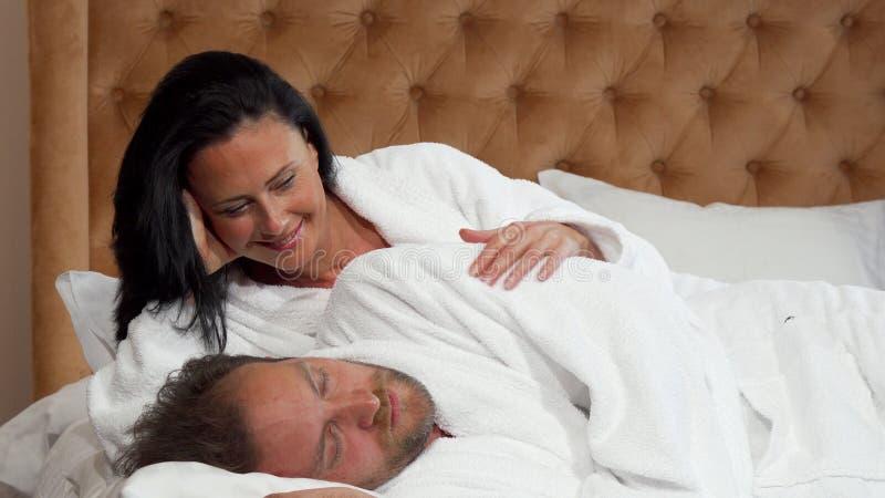 Hombre maduro que despierta a su esposa feliz hermosa, sonriendo en ella con amor imágenes de archivo libres de regalías