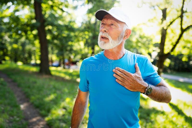 Hombre maduro que ejercita al aire libre para prevenir enfermedades cardiovasculares y ataque del corazón imagenes de archivo