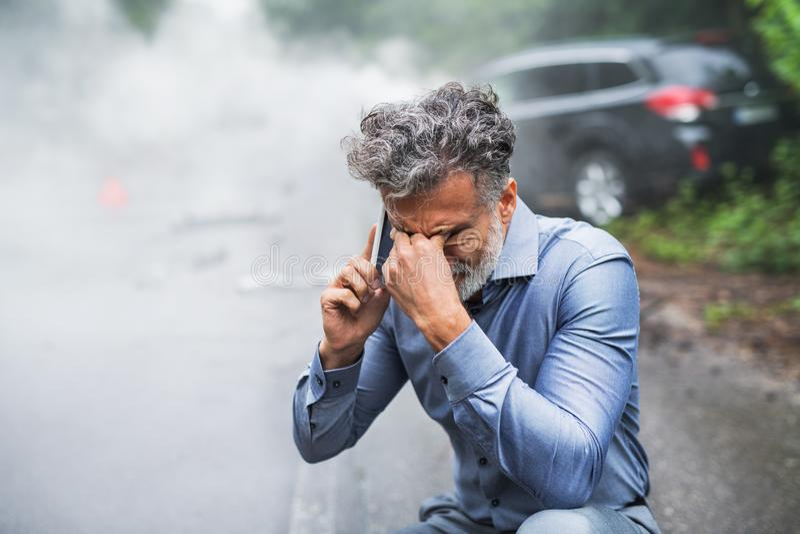 Hombre maduro que hace una llamada de teléfono después de un accidente de tráfico, humo en el fondo fotos de archivo libres de regalías