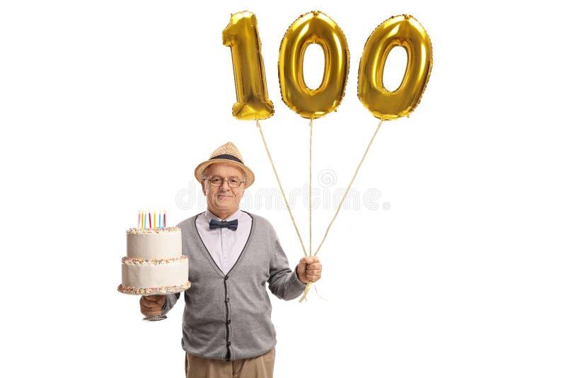 Hombre maduro que lleva a cabo una torta de cumpleaños y un bal de oro del número ciento imagen de archivo libre de regalías