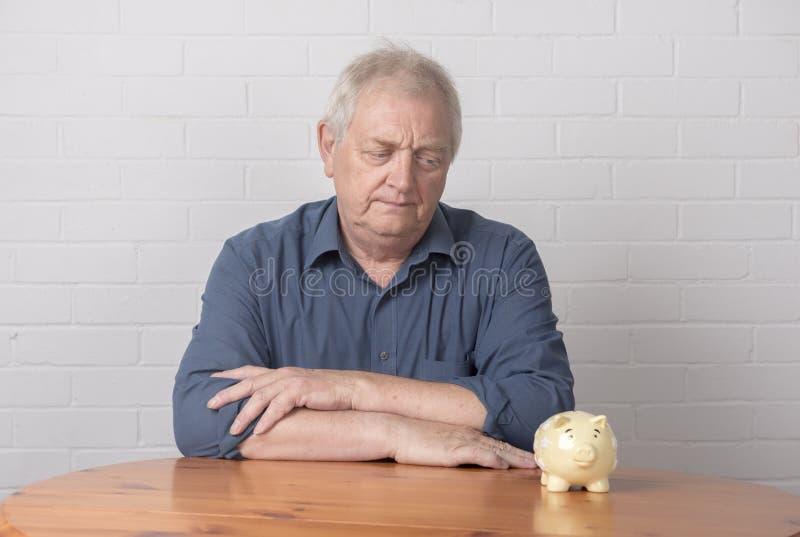Hombre maduro que mira una hucha fotografía de archivo