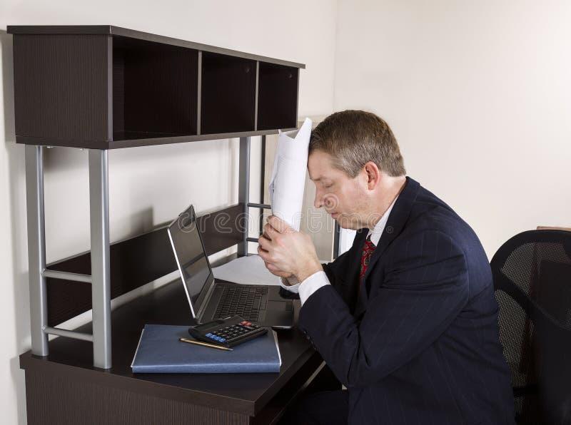 Hombre maduro que muestra la frustración de hacer impuestos sobre la renta imagen de archivo libre de regalías