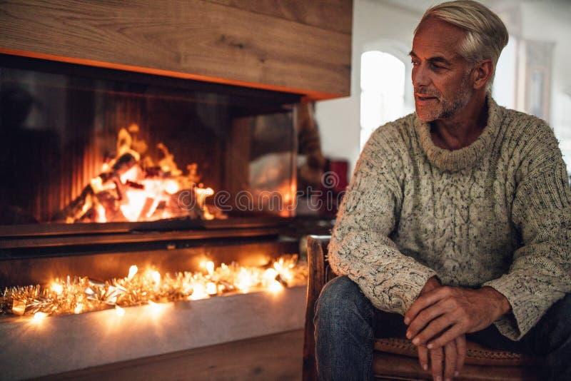 Hombre maduro que se sienta por el lugar del fuego en sala de estar fotografía de archivo
