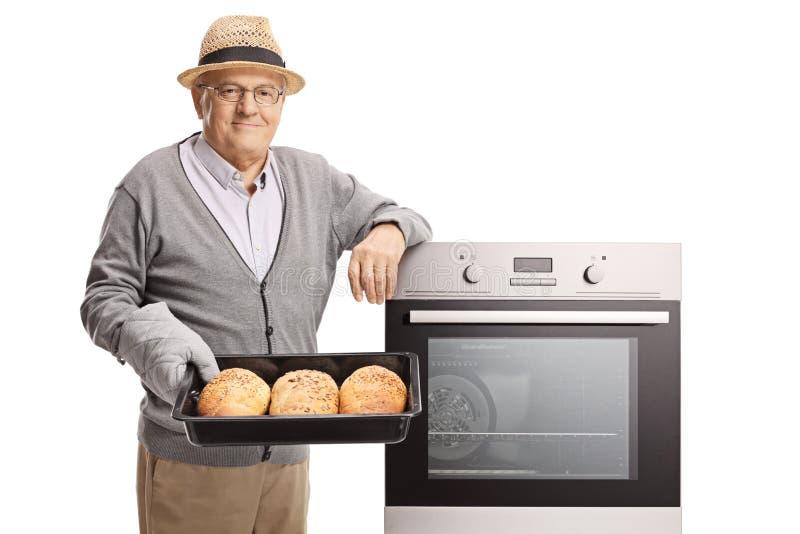 Hombre maduro que sostiene una bandeja con los panes recientemente cocidos del pan al lado de un horno fotografía de archivo