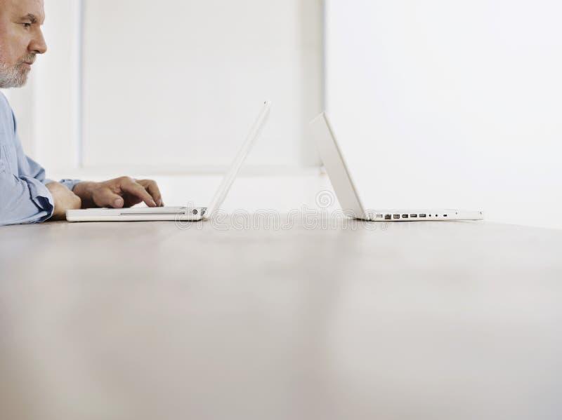 Hombre maduro que usa el ordenador portátil en la tabla imagenes de archivo