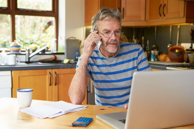 Hombre maduro que usa el teléfono móvil que mira en casa finanzas imágenes de archivo libres de regalías