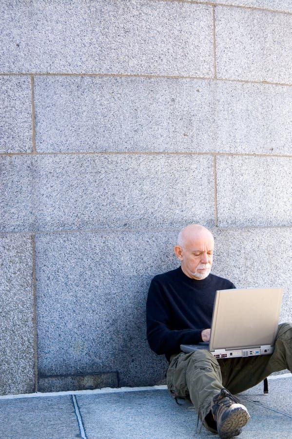 Hombre maduro que usa un ordenador fotos de archivo