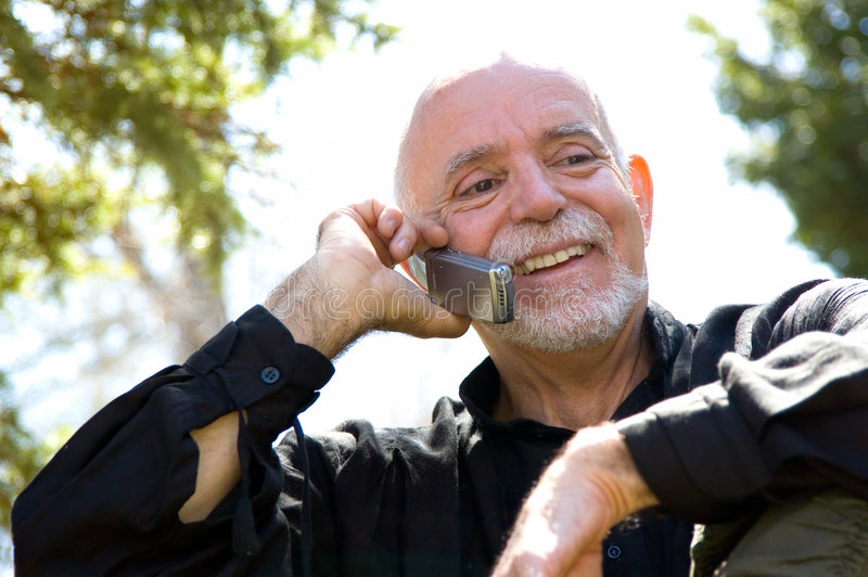 Hombre maduro que usa un teléfono celular imágenes de archivo libres de regalías