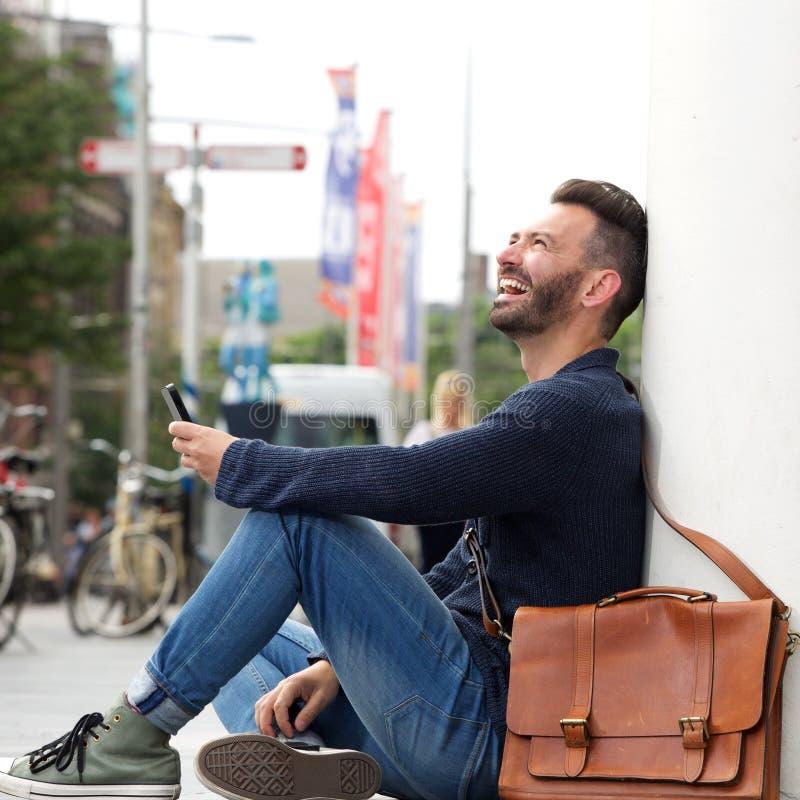 Hombre maduro relajado que sonríe con el teléfono celular imagenes de archivo