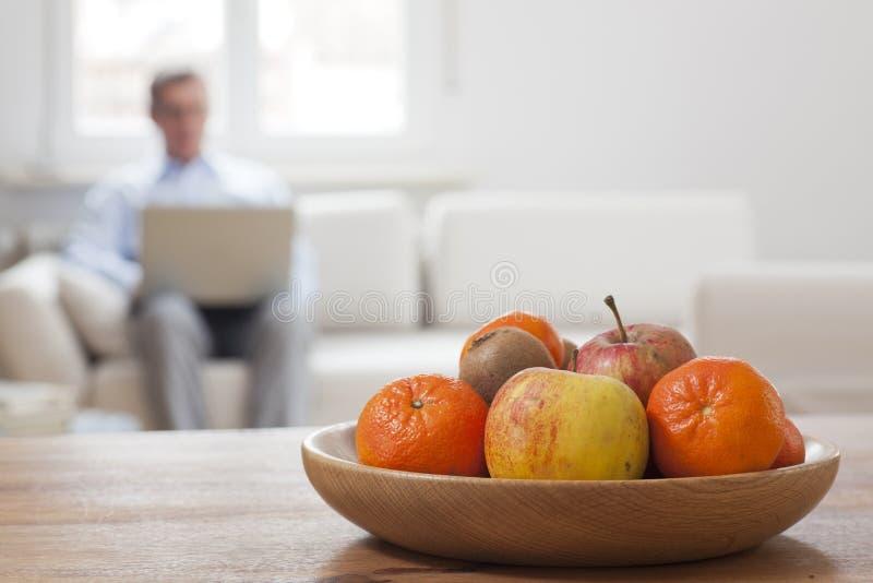 Hombre maduro sentado con un ordenador portátil en un salón con cuenco de fruta en primer plano imagen de archivo libre de regalías