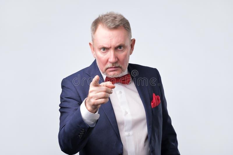 Hombre maduro serio confiado en formalwear que le señala imagen de archivo