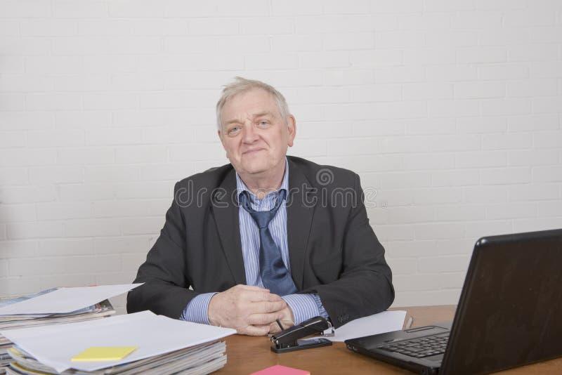 Hombre maduro sonriente en el trabajo foto de archivo libre de regalías
